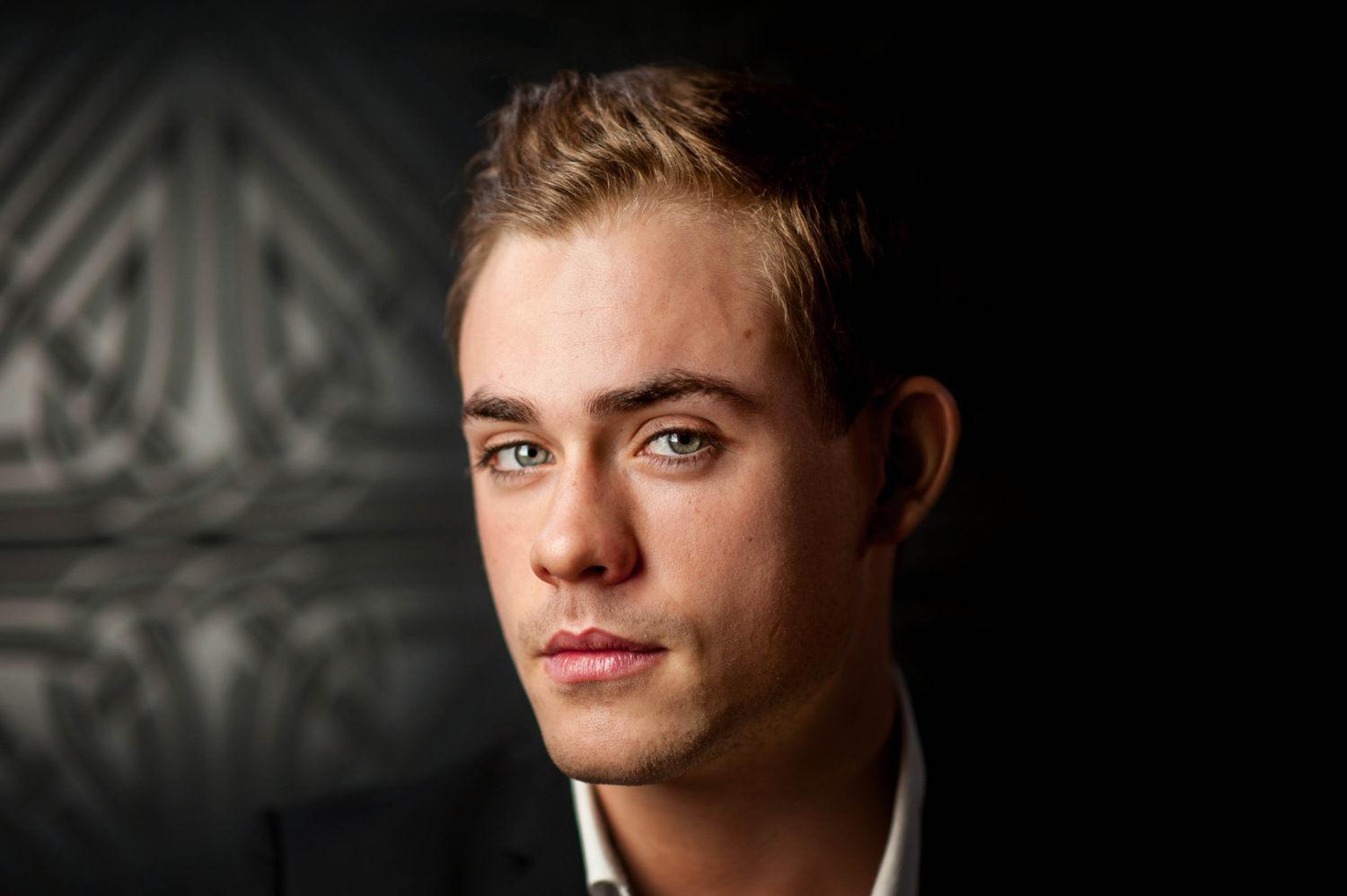 A young man with blond hair and blue eyes wearing a black suit