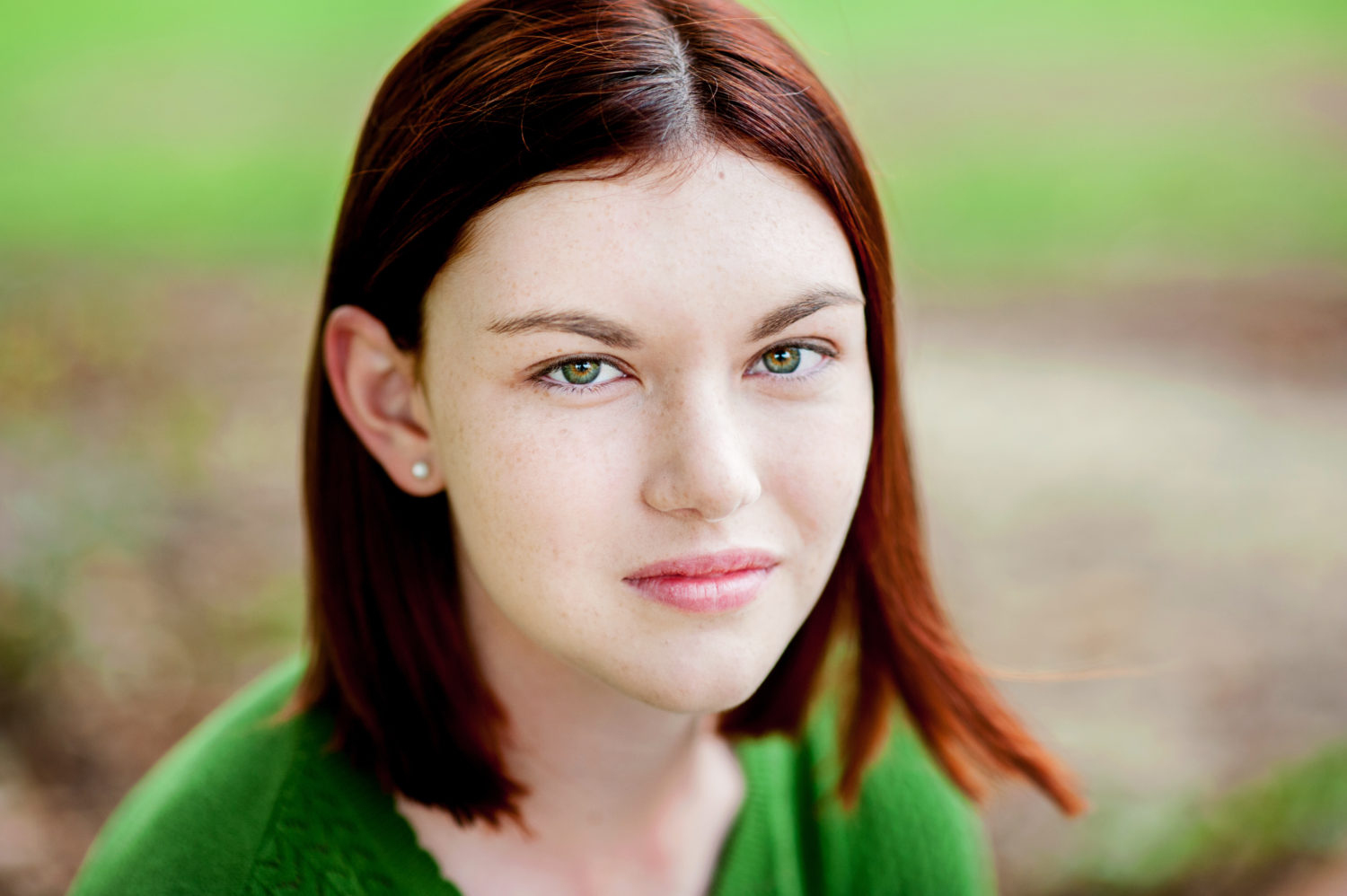 A young woman with red hair and green eyes wearing a green sweater